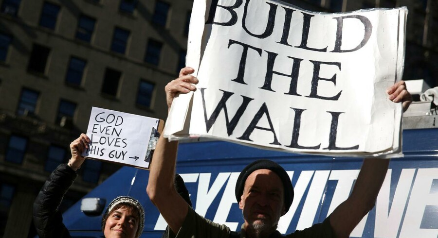 "Olivia Frazao (L) holds a ""God even loves this guy"" sign pointing toward U.S. President Donald Trump supporter Jim McDonald as he holds a ""Build the wall"" sign outside U.S. Citizenship and Immigration Services offices during a rally in support of immigration activist Ravi Ragbir (unseen) in New York, New York, U.S. March 9, 2017. REUTERS/Ashlee Espinal"