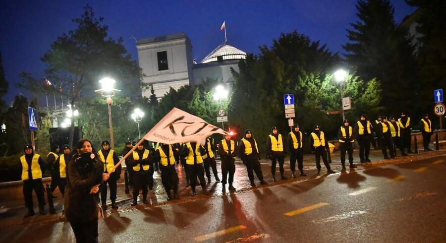 Politibetjente holder vagt foran parlamentet i Warzszawa, hvor tusinder af demonstranter i løbet af weekenden har protesteret mod Polens nationalkonservative regering.