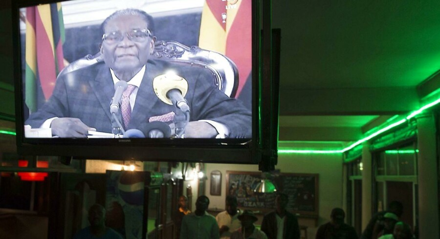 Zimbabweans watch a television broadcasting an address by President Robert Mugabe at Harare Sports Club in Harare on November 19, 2017, following a meeting with army chiefs who have seized power in Zimbabwe.. Zimbabwean President Robert Mugabe, in a much-expected TV address, stressed he was still in power after his authoritarian 37-year reign was rocked by a military takeover. Many Zimbabweans expected Mugabe to resign after the army seized power last week. But Mugabe delivered his speech alongside the uniformed generals who were behind the military intervention. In his address, Mugabe made no reference to the clamour for him to resign. / AFP PHOTO / STR