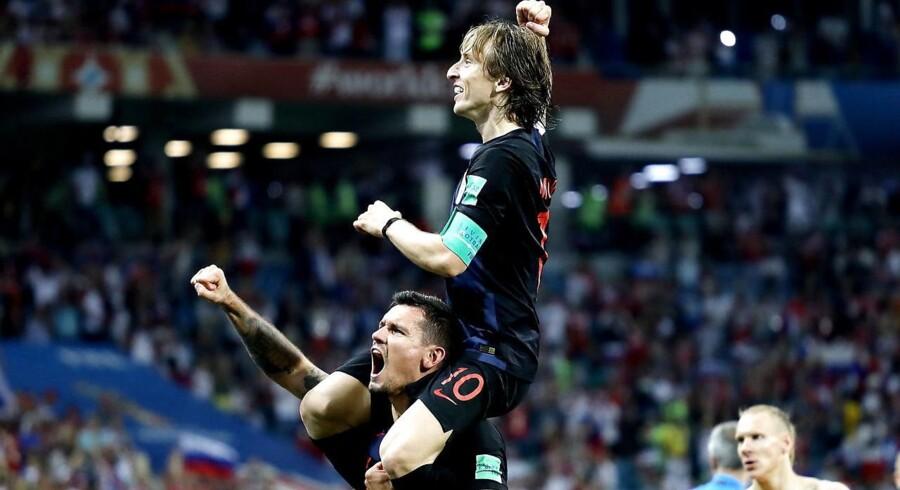 Kroatiens midtbanegeneral Luka Modrić fejrer sejren over Rusland sammen med forsvarsspilleren Dejan Lovren. Kroatien spiller semifinale mod England onsdag aften.