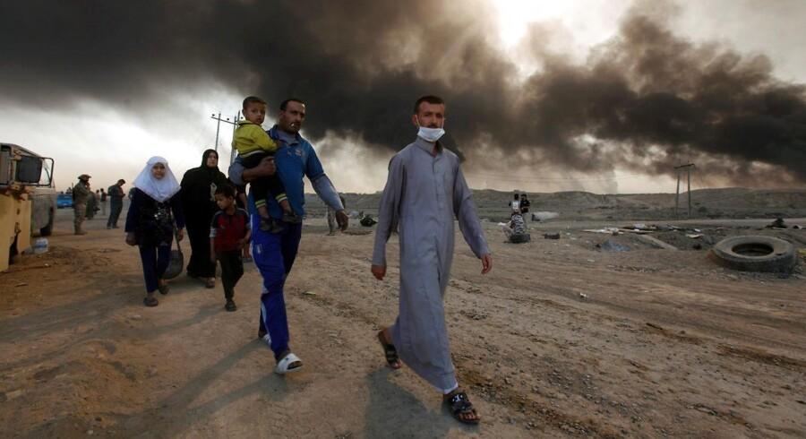 Civile irakere vender hjem til landsbyer som er blevet befriet fra Islamisk Stat, mens oliefelter brænder i baggrunden. REUTERS/Alaa Al-Marjani
