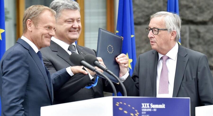 Ukraines præsident, Petro Porosjenko (i midten), fremviser stolt den underskrevne ratificering af associeringsaftalen mellem EU og Ukraine ved topmødet torsdag den 13. juli. EU var ved topmødet repræsenteret af formanden for Det Europæiske Råd, Donald Tusk (tv), og formanden for EU-Kommissionen, Jean-Claude Juncker (tv). / AFP PHOTO / Sergei SUPINSKY