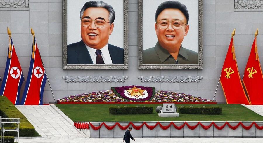 En mand går forbi portrætterne af Nordkoreas stifter, Kim Il-Sung, og sønnen Kim Jong-Il i det centrale Pyongyang.
