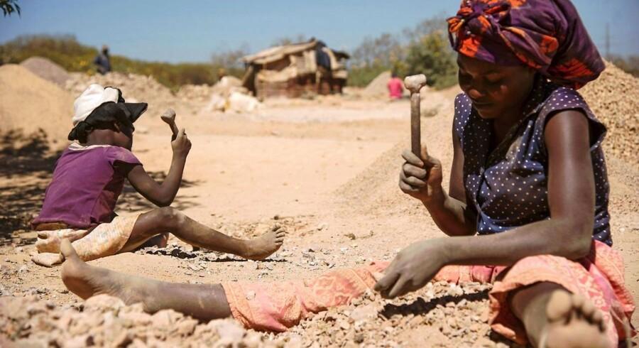 Et barn og en kvinde knuser klippesten fra en koboltmine i Lubumbashi i DR Congo, som er verdens største udvinder af metallet, der bruges i litium-ion-batterier. Arkivfoto: Junior Kannah, AFP/Scanpix