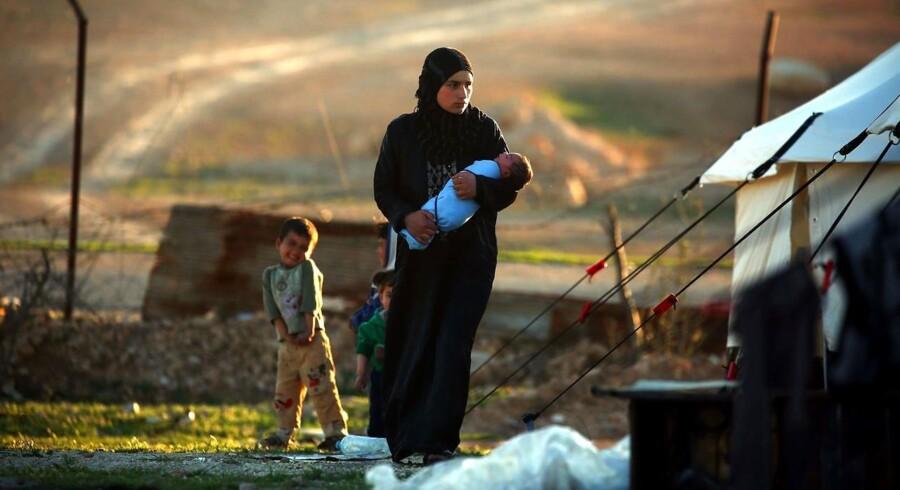 Arkivfoto af en syrisk kvinde med sine børn i en midlertidig flygtningelejr.