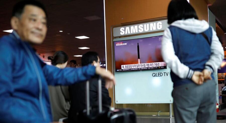 Folk ser nyheden om Nordkoreas seneste missilaffyring på et Samsung-TV på en togstation i Seoul i Sydkorea. Et angreb på Sydkorea kan stoppe verdens elektronikproduktion, fordi sydkoreanerne leverer de væsentlige dele af det meste udstyr. Arkivfoto: Kim Hong-Ji, Reuters/Scanpix