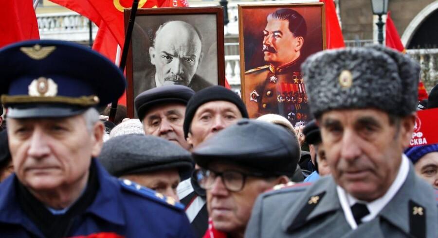 Russiske kommunister med sovjetiske flag og portrætter af Josef Stalin (th) og Vladimir Lenin (tv der fejrer 100-året for den russiske revolution. EPA/YURI KOCHETKOV