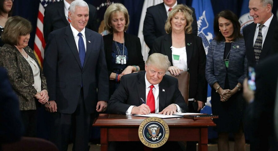 epa05750130 US President Donald J. Trump signs two executive orders during a visit to the Department of Homeland Security with Vice President Mike Pence, Homeland Security Secretary John Kelly (R) and other officials in Washington, DC, USA, 25 January 2017. Trump signed two executive orders related to domestic security and to begin the process of building a wall along the U.S.-Mexico border. EPA/Chip Somodevilla / POOL (AFP-OUT)