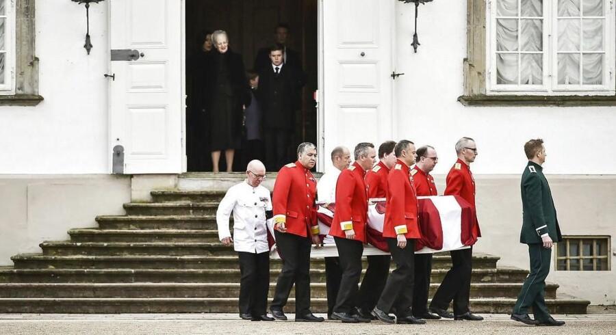 Dronning Margrethe og resten af Kongefamilien ser på, mens prins Henriks båre bliver båret ud i rustvognen.