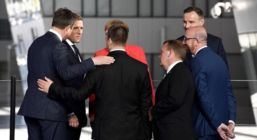 Frankrigs nye præsident, Emmanuel Macron, har allerede sendt klare beskeder til USAs præsident Trump og Ruslands præsident Putin i løbet af blot en måned i Élysée-palæet. Statsminister Lars Løkke Rasmussen (V) vil forsøge at knytte tættere bånd til Frankrig og Macron, når han onsdag er på besøg hos den franske præsident. Her ses Løkke og Tysklands kansler, Angela Merkel, mf. lytte til Macron under NATO-topmødet for to uger siden. / AFP PHOTO / Eric FEFERBERG