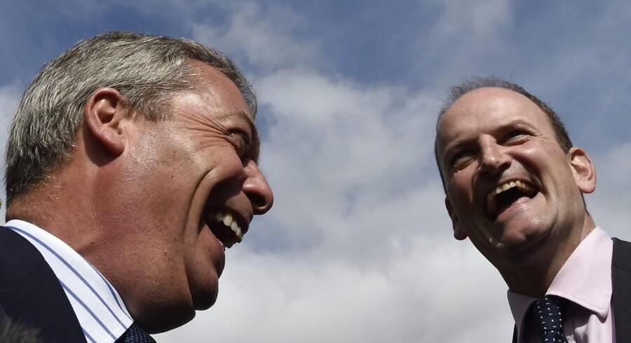 Så gode venner var de - aldrig. Nigel Farage (tv) og Douglas Carswell (th) smilede omkap, da de i 2014 fandt sammen i UKIP. Reelt havde de ikke meget andet end EU-modstanden tilfælles, og nu har de to excentriske, personligheder i britiske politik kastet sig ud i en åben strid, der skubber UKIP-partiet helt i baggrunden. Arkivfoto: Reuters