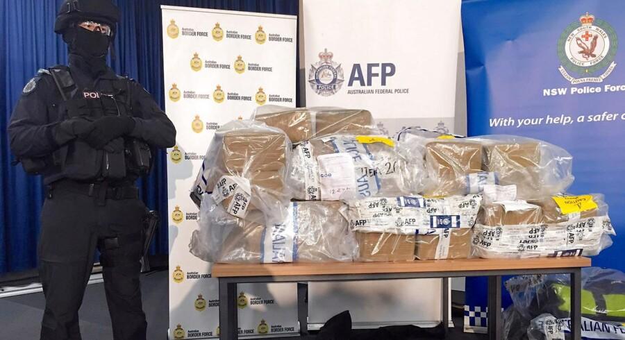 En bevæbnet australsk politimand står vagt ved 1,1 ton opbragt kokain, som blev fremvist på et pressemøde.