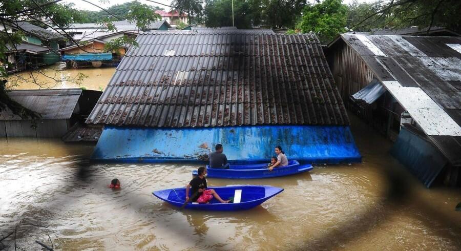 Beboere i Sungai Kolok området i det sydlige Thailand ses her 2. januar under oversvømmelser i Narathiwat. / AFP PHOTO / MADAREE TOHLALA