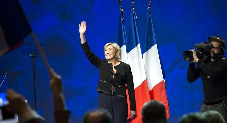 Marine Le Pen hilser på de omkring 5.000 deltagere ved sit indledende valgmøde i Lyon. EPA/ARNOLD JEROCKI