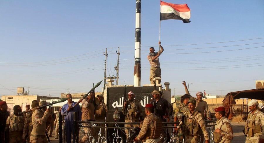 Irakiske regeringsstyrker rejser det irakiske flag, mens de fejrer at have renset et distrikt i Anbar-provinsen for Islamisk Stat, den 10. oktober 2016. De irakiske styrker planlægger en offensiv for at tage Mosul tilbage fra IS.