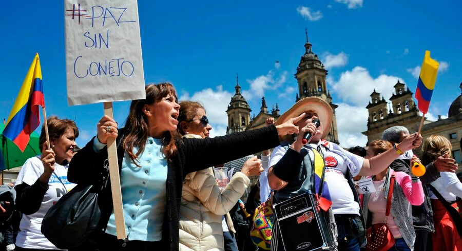 People shout slogans during a protest against the new peace agreement between the Colombian government and the FARC guerrilla, outside the Colombian Congress in Bogota, on November 30, 2016. Colombia's Congress is debating the government's controversial revised peace deal to end a half-century conflict with leftist FARC rebels after last month voters surprisingly snubbed an earlier version of the accord in a referendum. Now the government hopes to implement a revised accord through its majority in the legislature. / AFP PHOTO / GUILLERMO LEGARIA