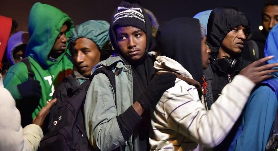 Migranter står i kø for at blive transporteret væk fra den store lejr med migranter og flygtninge i den franske havneby Calais.