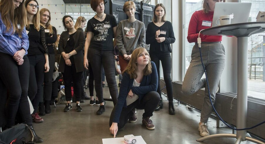 Første forsøg mislykkedes for Isabella Fink-Jensen (på gulvet), der er ved at få robotten Thymio til at tegne et hus med trekantet tag. Amanda Bastrup (ved computeren) hjælper med at ændre nogle af koderne, så det lykkes at få Thymio til at kreere et fint hus.