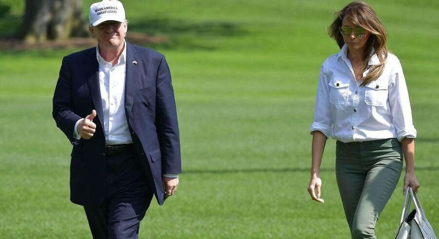 USAs præsident Donald Trump og hans kone Melania Trump går op mod Det Hvide Hus efter netop at være landet med helikopter fra Camp David, hvor de tilbragte deres weekend. Men ingen weekend uden debat om præsidenten. AFP PHOTO / MANDEL NGAN