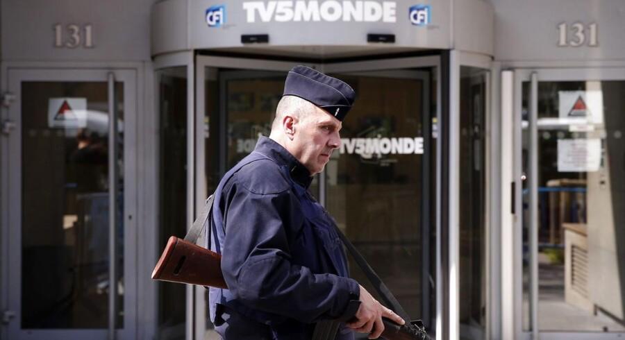 En fransk politibetjent står uden for TV 5 Monde, efter tv-stationen onsdag aften blev lagt ned af et cyberangreb. Der gik næsten 24 timer, før der igen kom programmer over skærmen.