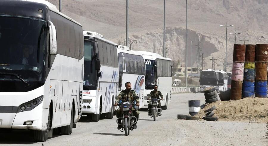 Syriske regeringstropper kører motorcykler forbi buser, der venter ved indgangen til Harasta i den østlige del af Ghouta. Busserne indholder oprørere og deres familier, som har fået lov til at forlade byen i en byttehandel, hvor 13 regeringssoldater blev løsladt af rebellerne.