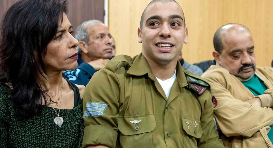Den israelske soldat Elor Azaria skød og dræbte en såret palæstinenser i marts 2016. Her ses han under en høring i den militære domstol, omgivet af sine forældre, moderen Oshra til venstre og faderen Charlie til højre. / AFP PHOTO / JACK GUEZ