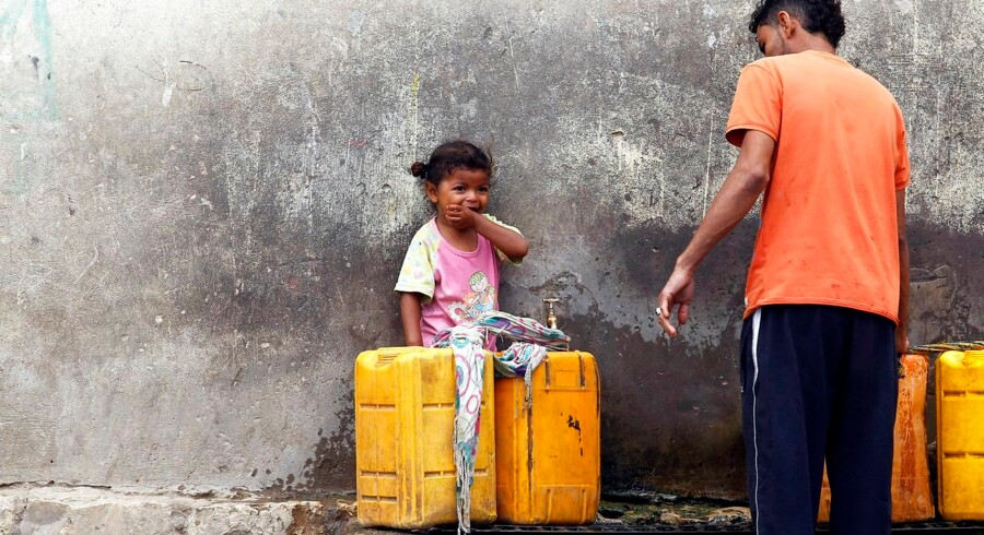 epa06062114 A Yemeni child (L) looks on as a man fills jerrycans with drinking water from a donated water pipe in Sana'a, Yemen, 02 July 2017. According to UNICEF and WHO reports, a rapidly spreading cholera outbreak in war-torn Yemen has claimed the lives of at least 1500 people since late April 2017 with another 246, 000 suspected cases across the impoverished Arab country, due to lack of access to clean water and a shortage of medical supplies. EPA/YAHYA ARHAB