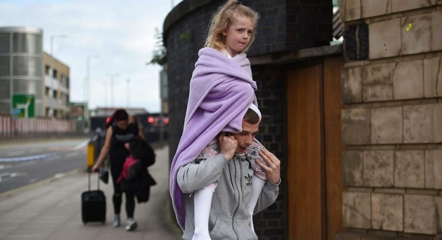 En mand bærer en pige på skuldrene efter angrebet i Manchester. Dansk terrorforsker mener, terroristerne eskalerer terroren, fordi vi er blevet immune overfor »normale« terrorhandlinger.