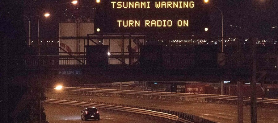 A tsunami warning alert is seen on a notice board above State Highway 1 in Wellington early on November 14, 2016 following an earthquake centred some 90 kilometres (57 miles) north of New Zealand's South Island city of Christchurch. A powerful 7.8 magnitude earthquake rocked New Zealand early November 14, the US Geological Survey said, prompting a tsunami warning and knocking out power and phone services in many parts of the country. / AFP PHOTO / Marty Melville