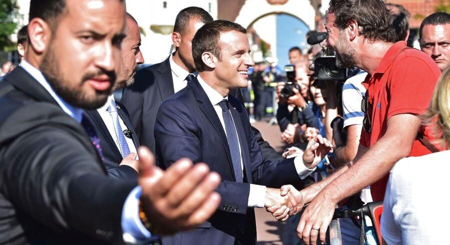 Emmanuel Macron hilser på en tilhænger efter at have stemt i den nordfranske badeby Le Touquet. Præsidenten får brug for al sin charme og politiske tæft, når han efter sejren ved søndagens nationalforsamlingsvalg nu skal i gang med at løse Frankrig problemer. AFP PHOTO / POOL / CHRISTOPHE ARCHAMBAULT
