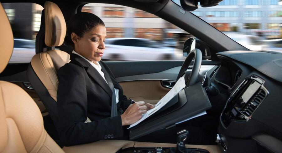 Volvo har udsendt dette foto af en kvindelig bilist, der kan læse og arbejde, mens hun sidder i en selvkørende bil. Volvo siger, fabrikken vil teste selvkørende biler i Storbritannien i 2017. Foto: Volvo/AFP