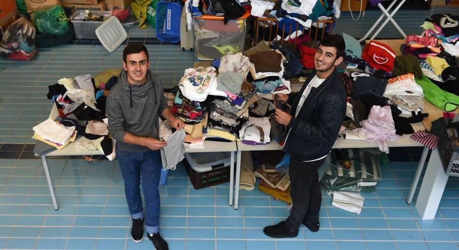 To irakiske immigranter, Peshtiwan Nasser Abdal (tv), og Suud-iazdxn Arab (th) kigger på tøj, som tyskere har doneret til flygtninge, der er indkvarteret i og ved en kirke i byen Tutzing i det sydlige Tyskland.