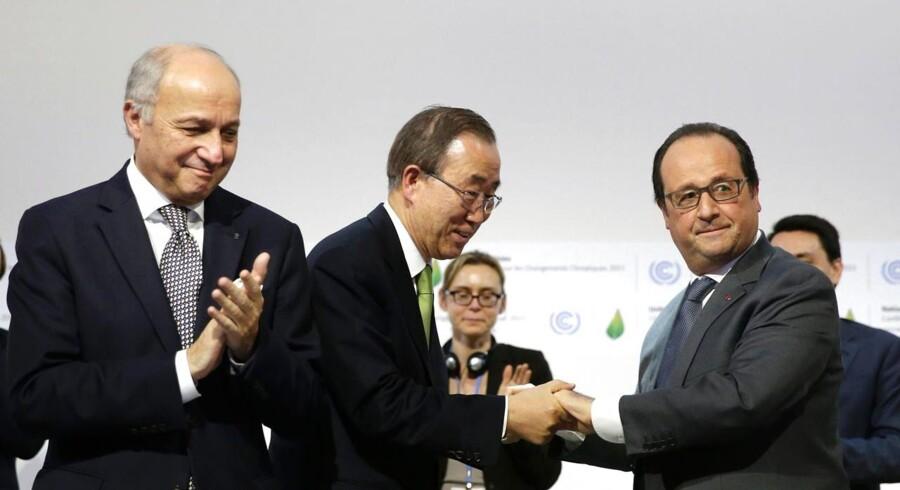 Den franske udenrigsminister og ledende kraft bag Parisaftalen, Laurent Fabius (tv.), klapper, mens FNs generalsekretær, Ban Ki-moon, trykker den franske præsident, Francis Hollande, på næven. Foto: Philippe Wojazer/AFP