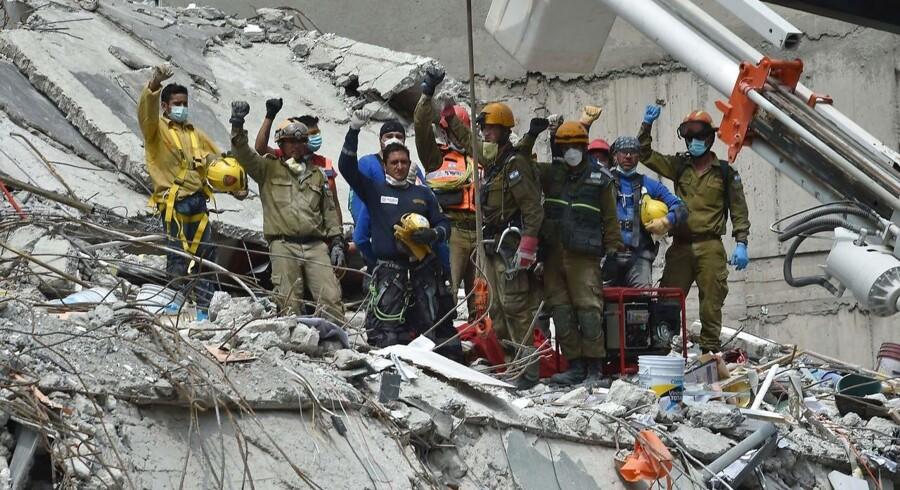Redningspersonale og brandmænd løfter deres næver som hyldest til en mand, der overlevede jordskælvet, men døde før redningspersonalet kunne nå frem til det sted, han var fanget, i en ødelagt bygning.