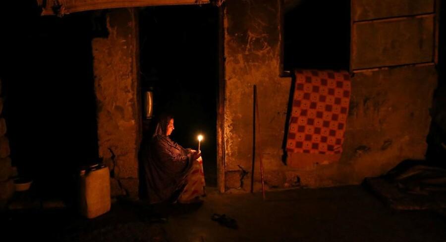 ARKIVFOTO: En palæstinensisk kvinde tænder et lys i sit hus under en strømafbrydelse i den sydlige del af Gazastriben.