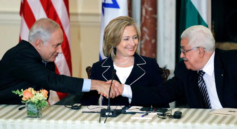 Under overværelse af USAs daværende udenrigsminister, Hillary Clinton, mødtes Israels premierminister, Benjamin Netanyahu (t.v.) med præsidenten for det palæstinensiske selvstyre, Mahmoud Abbas, under et møde i washington i 2010. I dag er der ikke nogen hjertelige miner mellem de to.