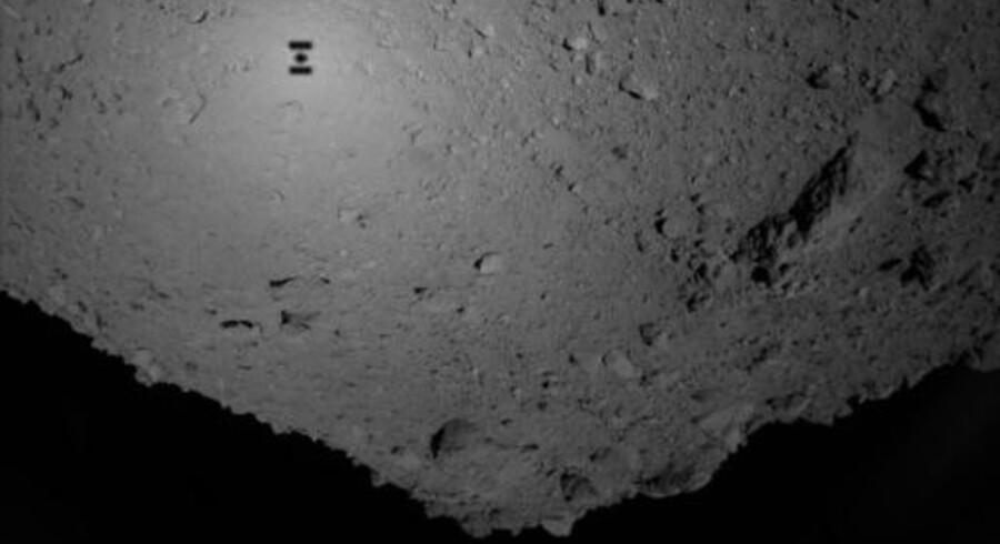 Den lille, men tydelige skygge på overfladen af den beskedne og arrede asteroide Ryugu stammer fra den japanske rumsonde Hayabusa-2, der i fredags landsatte to »springrobotter« i kagedåsestørrelse på himmellegemets overflade.