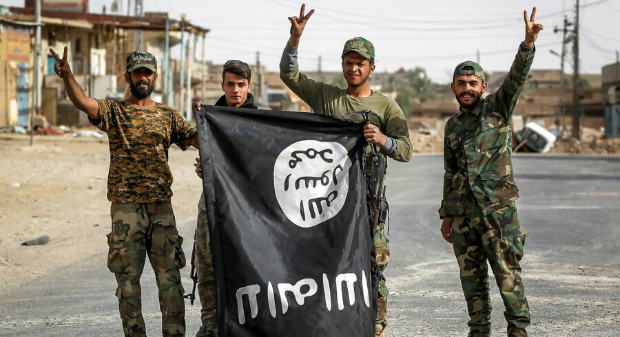 Irakiske medlemmer af Hashed al-Shaabi (Popular Mobilisation Units) vender et IS-flag på hovedet i Al-Qaim 3. november 2017.