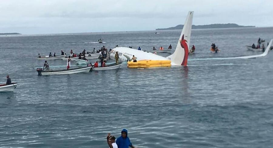 Både kommer passagerer og besætningsmedlemmer til undsætning, efter at flyet, en Boeing 737-800, rammer havet ud for den mikronesiske by Weno. Social Media/Reuters