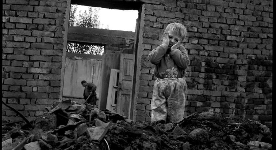 Familien Osmani i gang med genopbygningen af deres hus, der blev ødelagt af serberne. Et af børnene ses her udenfor huset.