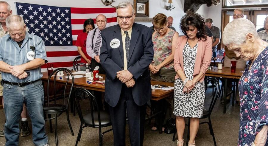 Inden Joe Arpaio går på, rejser alle sig op, folder hænderne og beder. Efter den fælles bøn fortæller Arpaio, at han er stolt over at være en af de første, som støttede Trump som præsidentkandidat fra sommeren 2015.
