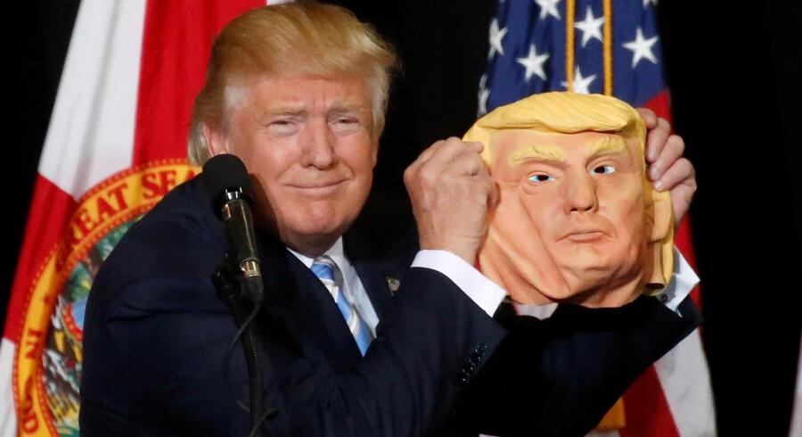 Donald Trump fremviser en maske af sig selv under et vælgermøde i Sarasota, 7. november. Foto: Carlo Allegri / Reuters