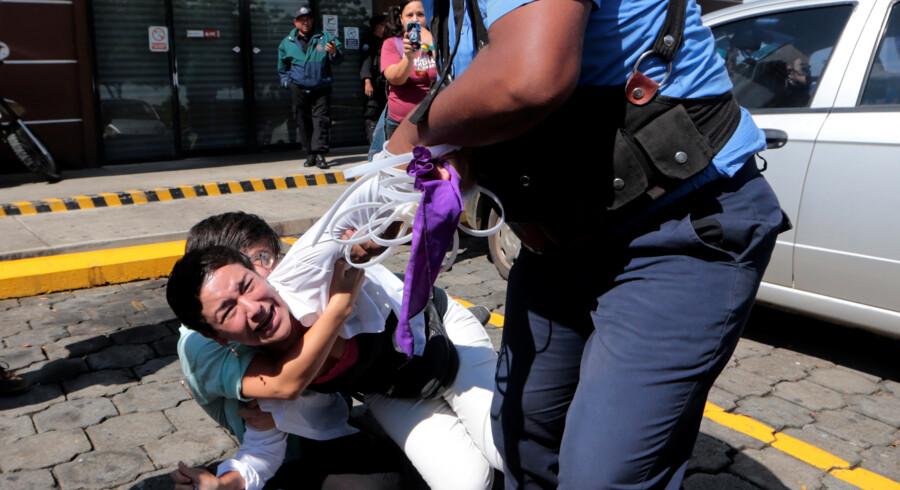 Politiet forsøger at anholde en kvinde under demonstrationen Sammen om frihed i Nicaraguas hovedstad, Managua, søndag. Oswaldo Rivas/Reuters