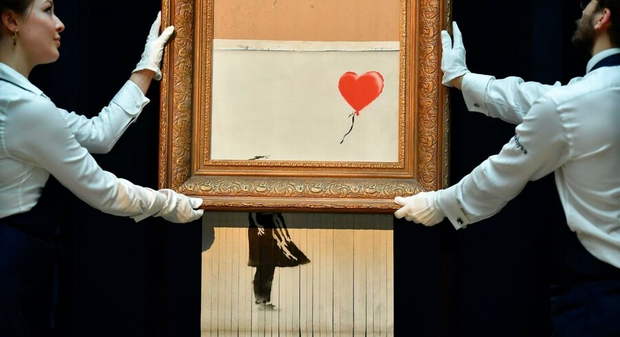 """Sotheby's employees pose with the newly completed work by artist Banksy entitled """"Love is in the Bin"""", a work that was created when the painting """"Girl with Balloon"""" was passed through a shredder in a surprise intervention by the artist, at Sotheby's auction house in London on October 12, 2018, following the work's sale. - The buyer of a work by street artist Banksy that was partially destroyed moments after it sold has gone through with the purchase, Sotheby's auction house said on October 11, 2018. The painting """"Girl with Balloon"""" was passed through a shredder hidden in the frame just after it went under the hammer last week for £1, 042, 000 ($1.4 million, 1.2 million euros). The modified version has now been certified by Banksy's authentication body Pest Control as a new piece of work in its own right, entitled """"Love is in the Bin"""". (Photo by Ben STANSALL / AFP) / RESTRICTED TO EDITORIAL USE - MANDATORY MENTION OF THE ARTIST UPON PUBLICATION - TO ILLUSTRATE THE EVENT AS SPECIFIED IN THE CAPTION"""