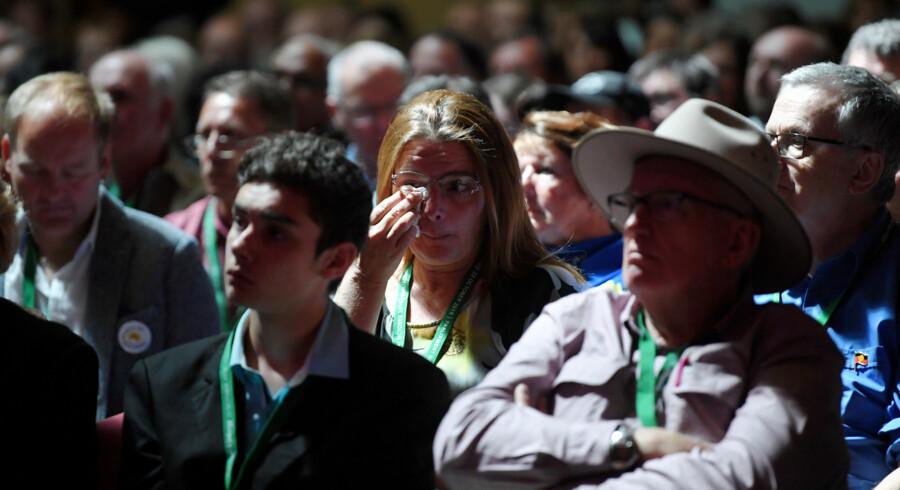 En kvinde på tilhørerpladser uden for parlamentet reagerer med tårer under den australske premierministers tale, hvor han giver en national undskyldning for årtiers misbrug af børn i landet. Handout/Reuters
