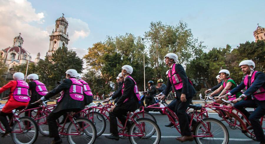 Foto: Hector Guerreo/AFP/Ritzau Scanpix. Borgmestre cykler i tandem under et C40-møde i Mexico City i 2016. Det er afgørende, at få verdens byer til at engagere sig, hvis vi skal gøre os håb om at sænke drivhusgasudledningerne.