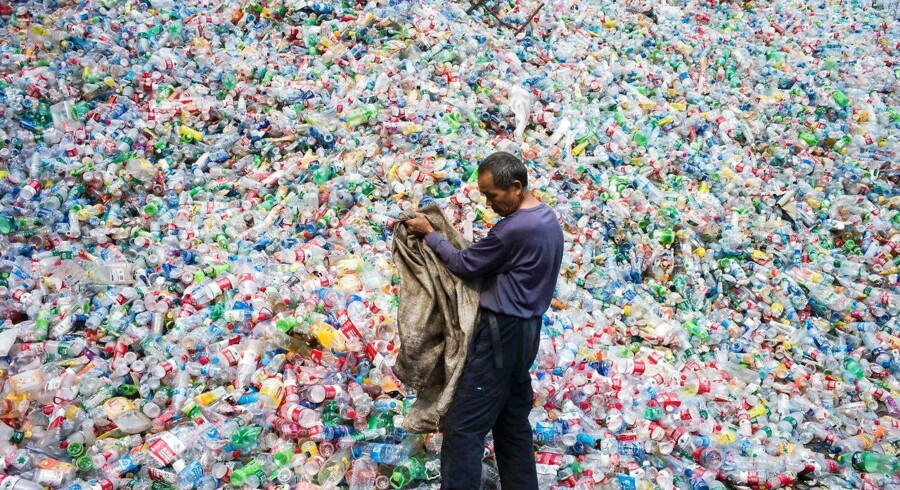TOPSHOT - This photo taken on September 17, 2015 shows a Chinese labourer sorting out plastic bottles for recycling in Dong Xiao Kou village, on the outskirt of Beijing. China is the world's biggest emitter of the greenhouse gases that cause climate change, and a crucial player in the global gathering finishing on December 11 in Paris, where nations have been trying to thrash out a plan to limit dangerous global warming. The 195-nation UN climate rescue talks in the French capital have been billed as the last chance to avert worst-case-scenario climate change impacts: increasingly severe drought, floods and storms, as well as island-engulfing rising seas. AFP PHOTO / FRED DUFOUR / AFP / FRED DUFOUR