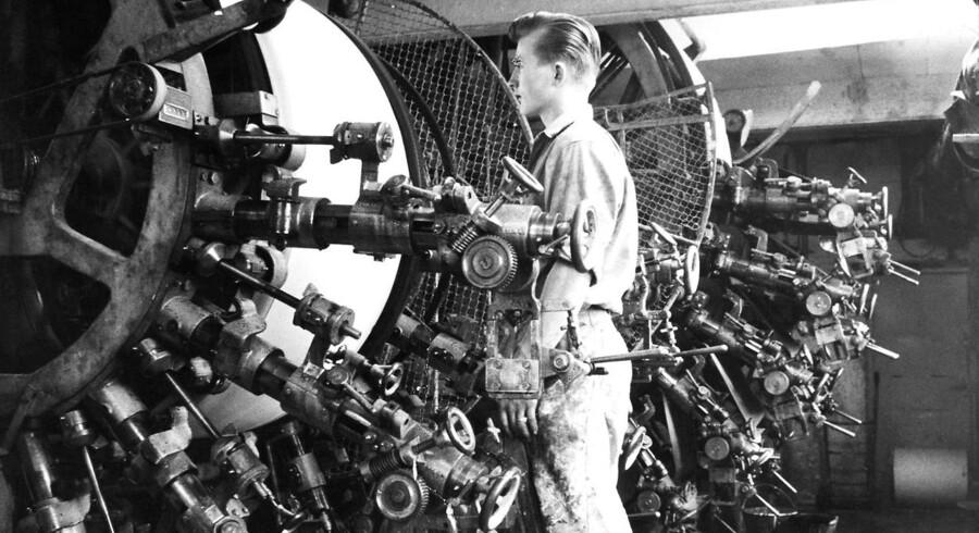 Ung arbejder passer sin maskine på tapetfabrik i 1962.