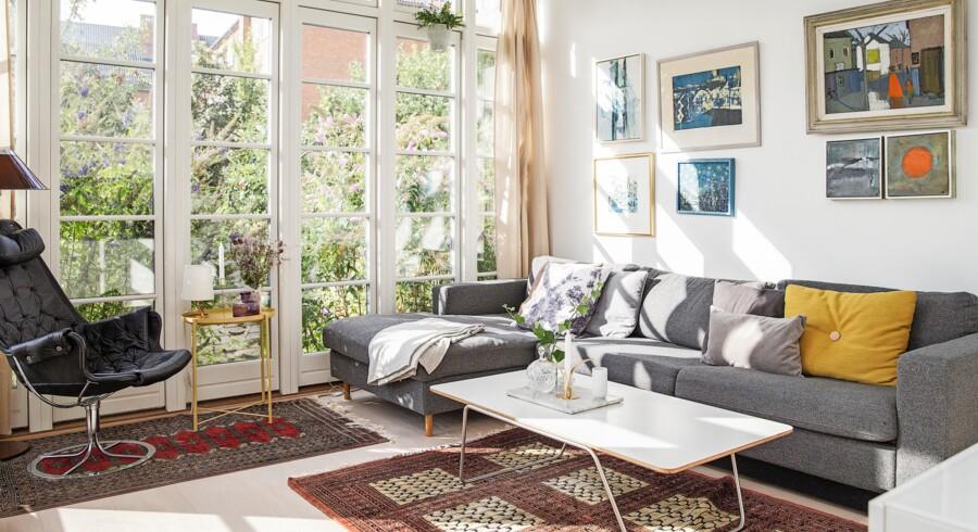Christina J. Jørgensen faldt for det magiske lysindfald fra det store vinduesparti her i stuen. Her kan man sidde i sofaen fra Bolia, og kigge ud på himlen. Puderne er fra bl.a. H&M Home, sofabordet er fra Hay, og gulvtæpperne er arvet. Bruno Mattson-lænestolen er også et arvestykke fra Claes Joakim Ossmarks morfar. På væggen hænger primært en del ældre malerier, der er arvestykker fra bl.a. Christina J. Jørgensens mor, blandet med hendes egne værker.