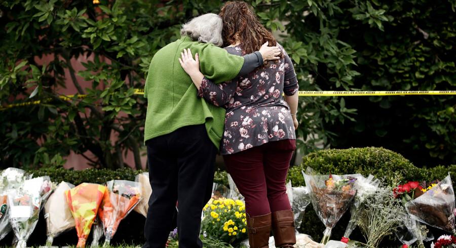 To personer støtter sig til hinanden foran blomster ved »Tree of Life Synagogue« i Pittsburgh, Okt.. 28, 2018. (AP Photo/Matt Rourke)